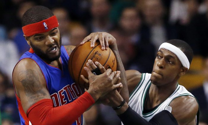 Detroit Pistons forward Josh Smith, left, and Boston Celtics guard Rajon Rondo fight for a loose ball during the first half of an NBA basketball game in Boston, Wednesday, Dec. 3, 2014. (AP Photo/Elise Amendola)