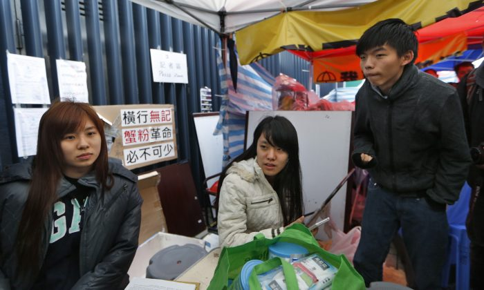 Three students, Joshua Wong (R), Prince Wong (C) and Isabella (L) Lo talk to the media during their hunger strike next to their tent at the occupied area outside government headquarters in Hong Kong Tuesday, Dec. 2, 2014. (AP Photo/Kin Cheung)