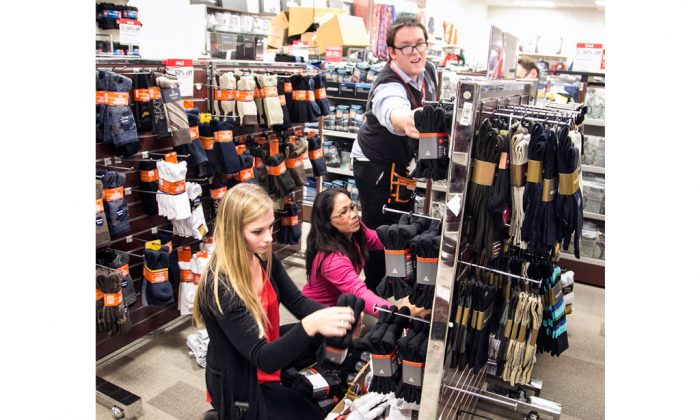 Towne East J.C. Penney employees (L-R) Tori Goldsmith, Carla Fuller and Brian Hill stock men's socks as they prepare for Thanksgiving Day sales, in Wichita, Kan., on Nov. 18, 2014. The Institute for Supply Management, a trade group of purchasing managers, issues its index of non-manufacturing activity for November on Wednesday, Dec. 3, 2014. (AP Photo/The Wichita Eagle, Mike Hutmacher)