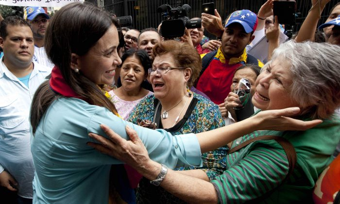 Former Congresswoman and opposition leader Maria Corina Machado (L) greets supporters as she exits the Attorney General Office in Caracas, Venezuela, Wednesday, Dec. 3, 2014. Machado appeared in court to testify after being charged with conspiring to assassinate Venezuela's President Nicolas Maduro. Machado, 47, was prohibited from leaving the country in June after she was removed from her National Assembly seat by the ruling party. (AP Photo/Ariana Cubillos)