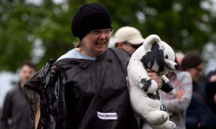 A woman holds a stuffed polar bear painted black to simulate oil during a protest against the Enbridge Northern Gateway Pipeline in Vancouver on May 10. NDP MP Nathan Cullen has introduced a bill that would ban tanker traffic in the areas of Dixon Entrance, Hecate Strait, and Queen Charlotte Sound. (The Canadian Press/Darryl Dyck)