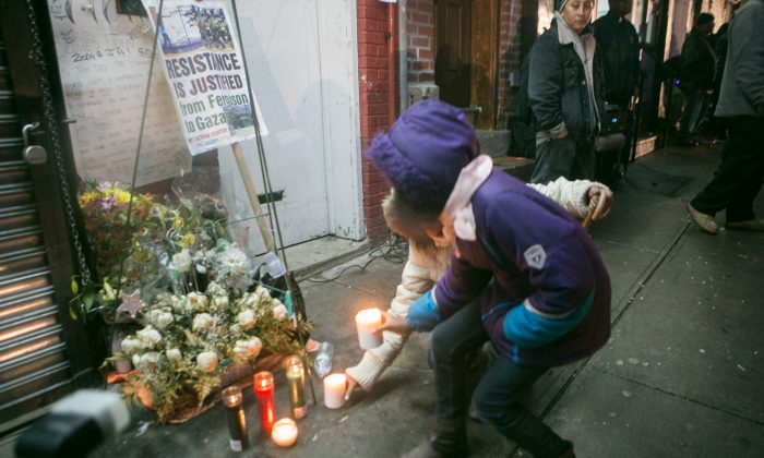 Children place candles on a memorial flowers at the location where Eric Garner was placed in a chokehold by a NYPD officer in Staten Island, on Wednesday. (Benjamin Chasteen/Epoch Times)
