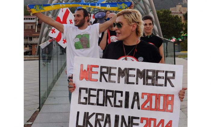 Protesters hold posters and shout slogans during a rally in support of Ukraine and against the Russian President Vladimir Putin, in Tbilisi, on Aug. 26, 2014. (Vano Shlamov/AFP/Getty Images)