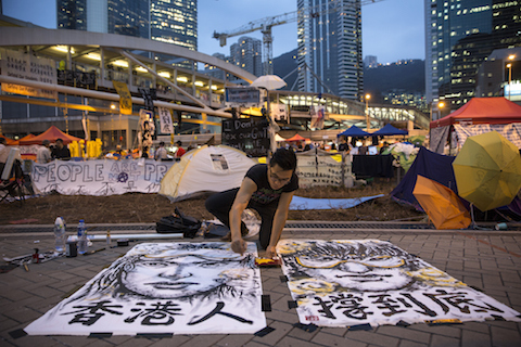 Artist Brian Chui who is a design consultant visiting from New York paints a female protester at the main protest site at Admiralty Oct. 24, 2014, in Hong Kong. (Paula Bronstein/Getty Images)