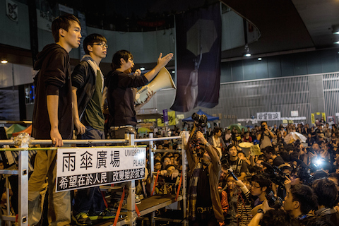 Student leader and pro-democracy activist Joshua Wong (2L) listens to speeches on stage during a rally on the streets outside Hong Kong's Central Government Complex on Nov. 21, 2014, in Hong Kong. (Chris McGrath/Getty Images)