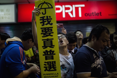 A pro-democracy protester (C) holds a sign for the Umbrella Movement as he shouts slogans in the Mongkok district of Hong Kong on Nov. 28, 2014. (Anthony Wallace/AFP/Getty Images)