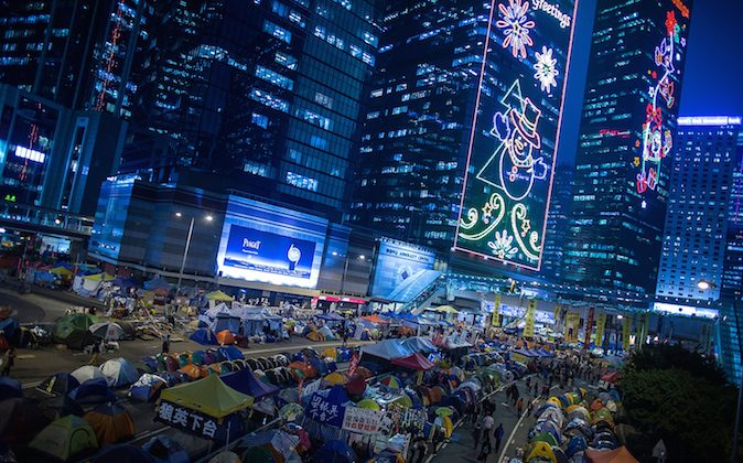 Pro-democracy protesters walk past tents at protest site in the Admiralty district on December 3, 2014 in Hong Kong. (Lam Yik Fei/Getty Images)