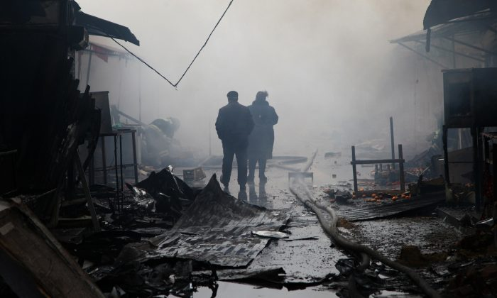 People walk past burnt out kiosks at a street market close to a destroyed building housing the housing the local media known as the Press House, in central Grozny, on Dec. 4, 2014. Heavily-armed gunmen attacked a police post killing several officers before storming a building housing the local media and a school in the capital. (Elena Fitkulina/AFP/Getty Images)
