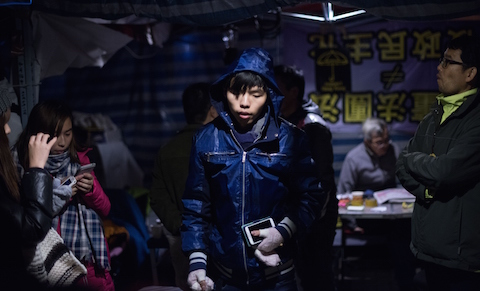 Leader of the student group Scholarism, Joshua Wong (C) arrives for a press conference at the pro-democracy movement's main protest site in the Admiralty district of Hong Kong on Dec. 4, 2014. (Johannes Eisele/AFP/Getty Images)