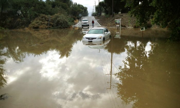 A car sits partially submerged in flood waters on Hemet Street in Hemet, Calif., Thursday morning, Dec. 4, 2014, after overnight rains doused the area. A second day of much-needed rain is falling across drought-stricken California. (AP Photo/The Press-Enterprise, Craig Shultz)