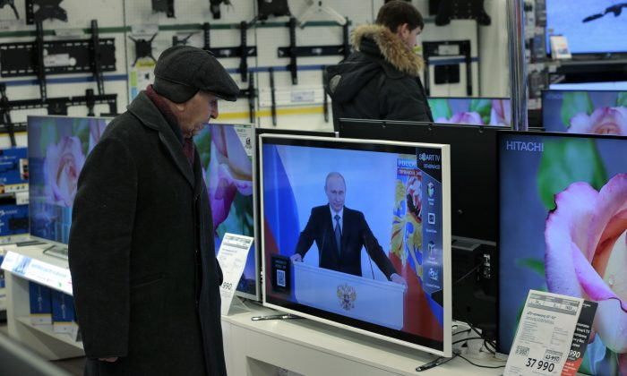 Customers look at TV sets with Russian President Vladimir Putin, at a shop in Moscow, Russia, on Thursday, Dec. 4, 2014, during his annual state of the nation address in the Kremlin. Russian President Vladimir Putin has defended the Kremlin's aggressive foreign policy, saying the actions are necessary for his country's survival. (AP Photo/Ivan Sekretarev)