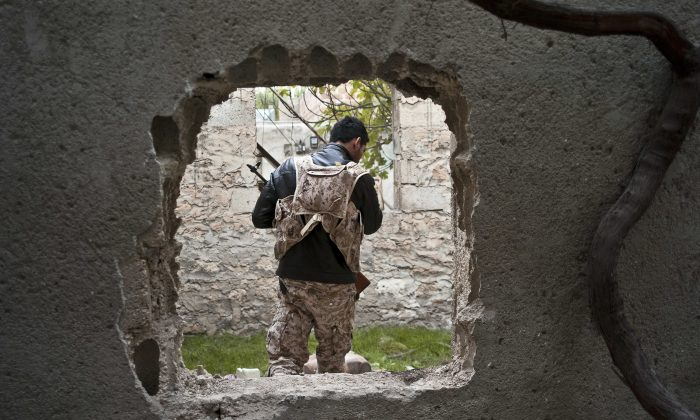 In this Nov. 1, 2014 photo, a fighter from the coalition against the Islamic State group is seen through a hole cut in a wall to create shortcuts in the battlefield in Kobani, Syria.  In a surprising display of resilience, the Kurdish fighters have held out against the more experienced jihadists more than two months into the Islamic State group militants' offensive on the frontier town, hanging on to their territory against all expectations.(AP Photo/Jake Simkin)