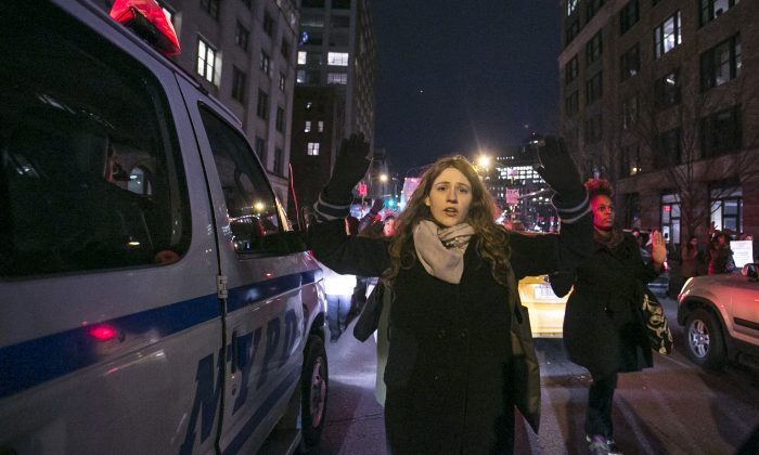 A protester puts her hands up in solidarity with Eric Garner, the black unarmed man who died after being put in a chokehold by a white police officer, during protests on Dec. 4, 2014 in Manhattan, New York. (Samira Bouaou/Epoch Times)