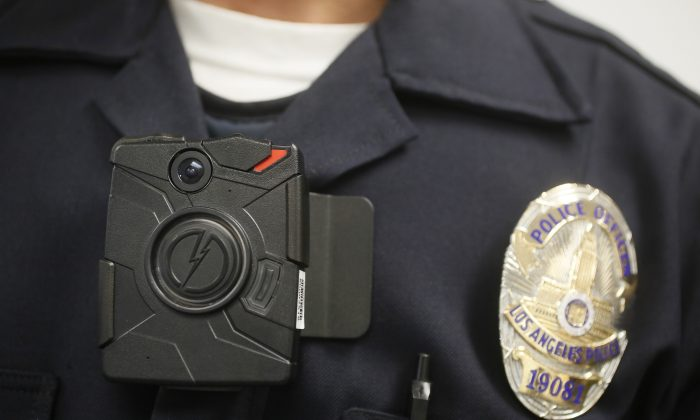 FILE-This Jan. 15, 2014 file photo a Los Angeles Police officer wears an on-body cameras during a demonstration for media in Los Angeles. Officers in one of every six departments around the country are now patrolling with these tiny cameras on their chests, lapels or sunglasses, and that number is growing. Most civil libertarians support their expansion despite concerns about the development of policies governing their use and their impact on privacy. (AP Photo/Damian Dovarganes,File)