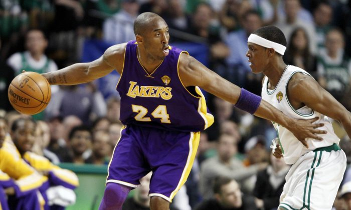 Los Angeles Lakers' Kobe Bryant looks for an opening around Boston Celtics' Rajon Rondo during Game 4 of the NBA basketball finals, Thursday, June 10, 2010, in Boston. (AP Photo/Winslow Townson)