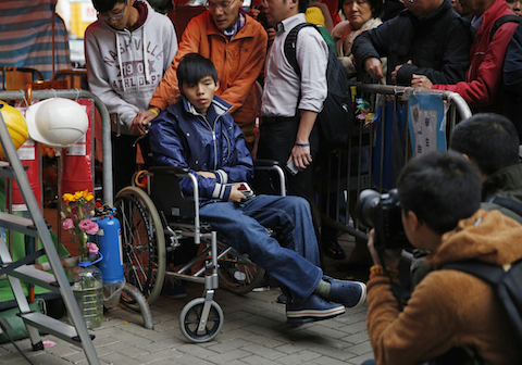 Student leader Joshua Wong attends a news conference as he sits on a wheel chair during a hunger strike at the occupied area outside government headquarters in Hong Kong on Friday, Dec. 5, 2014. (AP Photo/Kin Cheung)