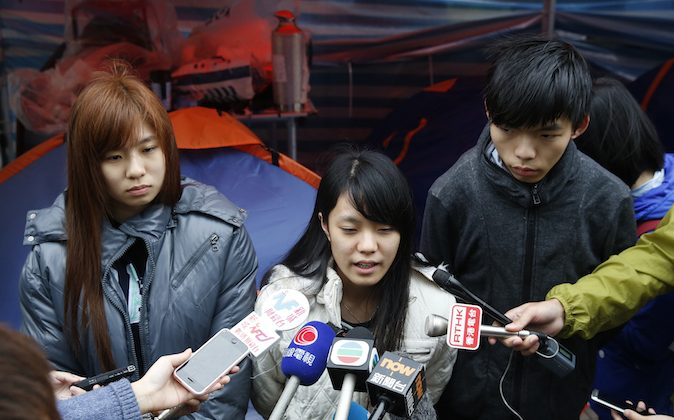 Three students, from right, Joshua Wong, Prince Wong and Isabella Lo speak to the media during their hunger strike at the occupied area outside government headquarters in Hong Kong on Tuesday, Dec. 2, 2014. (AP Photo/Kin Cheung)