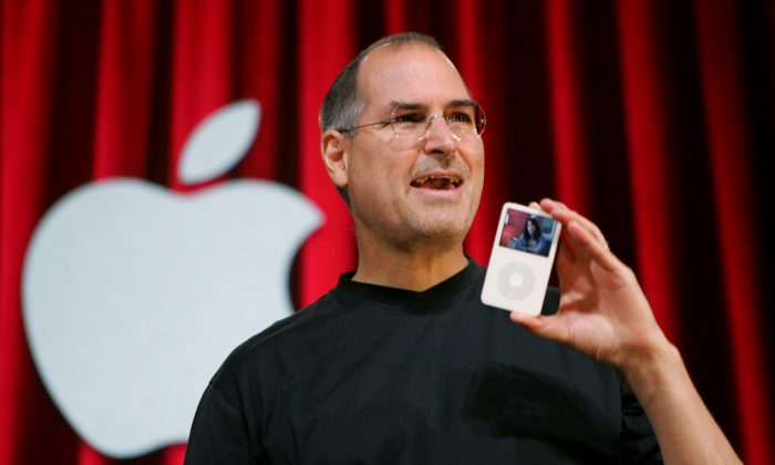 Apple Computer Inc. CEO Steve Jobs holds up an iPod during an event in San Jose, Calif., on Oct. 12, 2005. Jurors in a class-action lawsuit against Apple Inc. on Tuesday, Dec. 2, 2014, saw emails from the late CEO and his top lieutenants that show Jobs was determined to keep Apple's popular iPod music players free from songs that were sold by competing online stores. (AP Photo/Paul Sakuma)