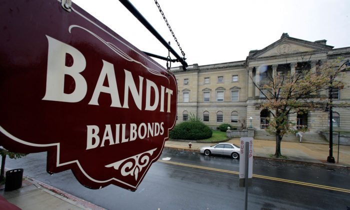 A sign is seen outside a bail bondsman across the street from Mercer County criminal courthouse in Trenton, N.J., on Oct. 23, 2014. In courtrooms across the country every day, a price tag is put on freedom and for many it's too expensive. With more than 60 percent of inmates in jails nationwide awaiting trial and many unable to afford bail, some states and counties are looking at overhauling the system so it's based less on money and more on holding dangerous defendants. Earlier this year, New Jersey became the latest state to adopt a system that bases bail on a risk analysis of each defendant. (AP Photo/Mel Evans)