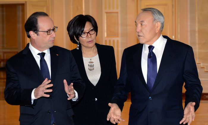 Kazakh President Nursultan Nazarbayev (R) and French President Francois Hollande speak during their meeting in Astana, Kazakhstan, Friday, Dec. 5, 2014. Unidentified aid as centre. (AP Photo/Sergei Bondarenko, Presidential Press Service)