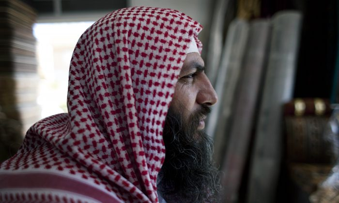 Salafi cleric Mohammed al-Shalabi, 48, widely known as Abu Sayyaf, talks during an interview with the Associated Press at a furniture store, owned by the head of Abu Sayyaf's clan, in the city of Ma'an, Jordan, on Oct. 29, 2014. Local authorities quickly stripped away public signs of support for the Islamic State group in this desert town. Black flags have been removed from rooftops. Graffiti proclaiming the extremists' imminent victory have been whitewashed. But supporters of the Middle East's most radical extremist group are only laying low. (AP Photo/Nasser Nasser)