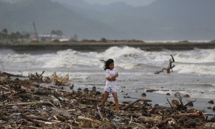 A girl walks along the shore as strong waves from Typhoon Hagupit hit Atimonan, Quezon province, eastern Philippines on Saturday, Dec. 6, 2014. Haunted by Typhoon Haiyan's massive devastation last year, more than 600,000 people fled Philippine villages and the military went on full alert Saturday to brace for a powerful storm only hours away from the country's eastern coast. (AP Photo/Aaron Favila)