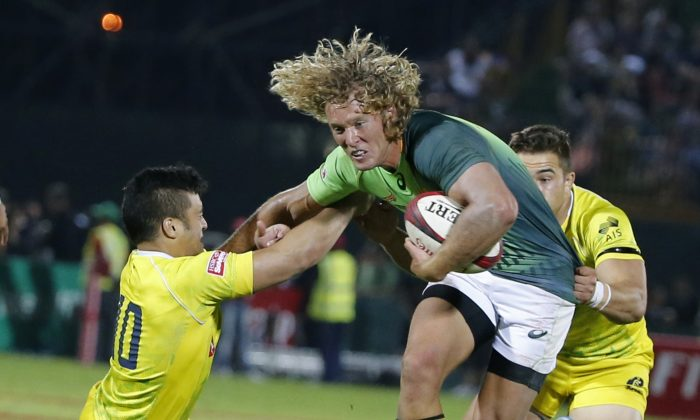 Werner Kok (C) of South Africa is tackled by Allan Faalavaau (L) and Greg Jeloudev of Australia during the final of the Emirates Airlines Dubai Sevens on December 6, 2014. The 2014/15 World Seven Series began in Australia's Gold Coast last month and will now see the 16 teams move on to Port Elizabeth, South Africa for the next leg of the series to be played this coming weekend Dec 13-14. (KARIM SAHIB/AFP/Getty Images)