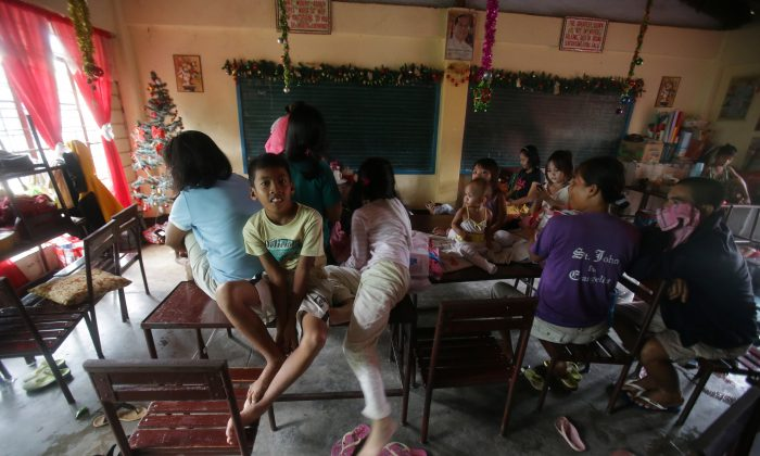 Evacuees stay inside a school as Typhoon Hagupit affects Legazpi, Albay province, eastern Philippines on Sunday, Dec. 7, 2014. (AP Photo/Aaron Favila)