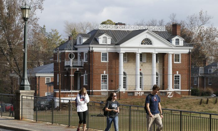 Students walk to campus past the Phi Kappa Psi fraternity house at the University of Virginia in Charlottesville, Va. on Nov. 24. Rolling Stone published a story alleging a rape by seven members of Phi Kappa Psi in November. (AP Photo/Steve Helber)