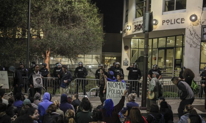 Demonstrators protest in front of the Berkeley police station in Berkeley California on Saturday, Dec. 6, 2014. Two officers were injured Saturday night as a California protest over police killings turned violent with protesters smashing windows and throwing rocks and bricks at police, who responded by firing tear gas, authorities said. Demonstrators were responding to the grand jury verdicts in the shooting death of Michael Brown in Ferguson, Missouri and the chokehold death of Eric Garner in New York City by local police officers in their communities. (AP Photo/San Francisco Chronicle, Sam Wolson)