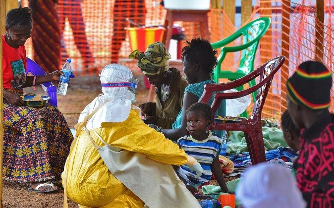 An MSF medical worker feeds an Ebola child victim. (Carl de Souza/AFP/Getty Images)