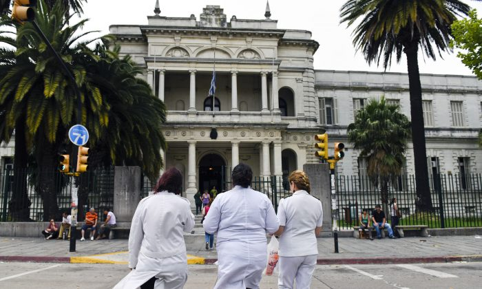 Three doctors enter the military hospital in Montevideo, Uruguay, Sunday, Dec. 7, 2014. (AP Photo/Matilde Campodonico)