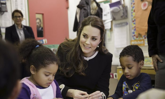 Kate, the Duchess of Cambridge, sits next to four-year-olds April, left, and Sammy in a pre-school class at the Northside Center for Childhood Development, Monday, Dec. 8, 2014 in New York. Kate and Prince William arrived in New York City on Sunday, their first official visit to the U.S. since a 2011 trip to California and their first taste of the Big Apple.(AP Photo/Seth Wenig, Pool)