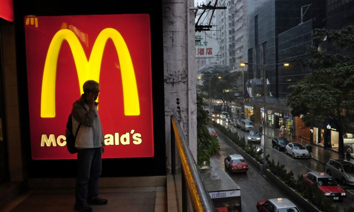 An article saying McDonald's is removing the Big Mac, Apple Pies, and large size options isn't real.  In this April 2, 2014, file photo, a man talks on a mobile phone next to a downtown McDonald's in Hong Kong. McDonald's says a key global sales figure fell 2.2 percent in November 2014 as U.S. sales continue to soften and it contends with ongoing difficulties from a food-safety scandal in China. (AP Photo/Vincent Yu, File)