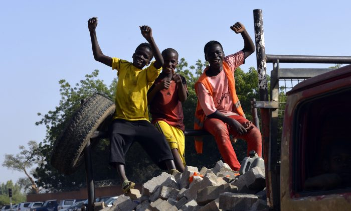 Children cheer while traveling on a truck loaded with stones in Niamey, Niger, on Nov. 23, 2014. (Miguel Medina/AFP/Getty Images)