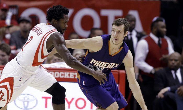 Phoenix Suns' Goran Dragic (1) is pressured by Houston Rockets' Patrick Beverley (2) in the second half of an NBA basketball game Saturday, Dec. 6, 2014, in Houston. (AP Photo/Pat Sullivan)