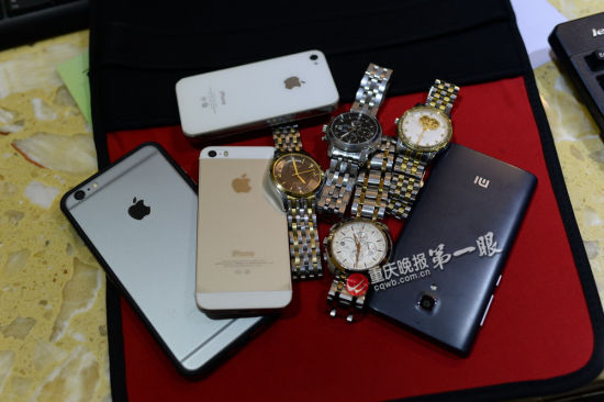 Phones and watches owned by four men who begged money on street in Chongqing City are displayed at the local police station. Four Chinese men begging for money on street were detained by police after a resident reported them for swindling money, on Dec. 6, 2014. (Screenshot/Chongqing Evening News)
