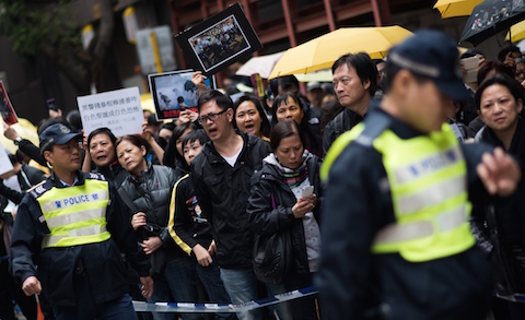 Demonstrators speak to a police officer in a march against police brutality during the pro-democracy protests, in the Wan Chai district of Hong Kong on December 7, 2014. (Johannes Eisele/AFP/Getty Images)
