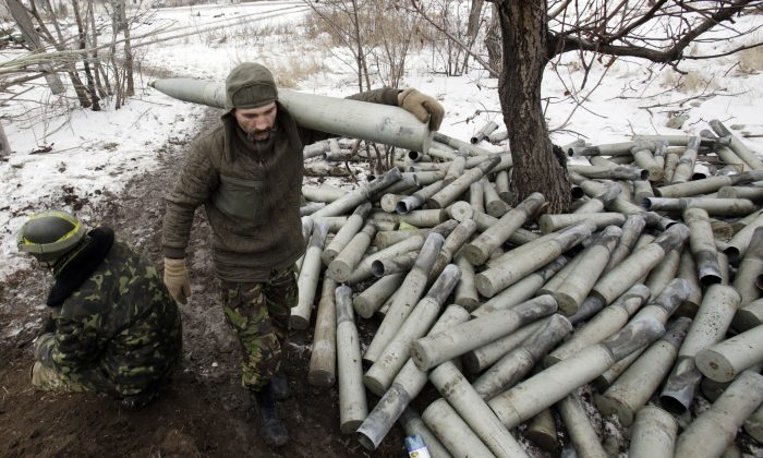 A Ukrainian artilleryman carries a shell past spent shell cases at their position near the eastern Ukrainian village Pisky, Donetsk region, to be fired at the position of pro-Russia separatists at Donetsk airport on Dec. 8, 2014. (Anatolii Stepanov/AFP/Getty Images)