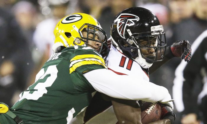 Green Bay Packers' Micah Hyde tackles Atlanta Falcons' Julio Jones (11) after a catch during the first half of an NFL football game Monday, Dec. 8, 2014, in Green Bay, Wis. (AP Photo/Tom Lynn)
