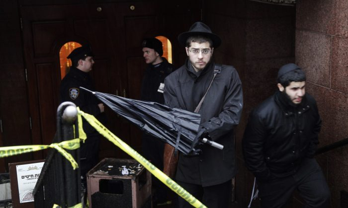 A member of the Lubavitch community, center, leaves the Chabad-Lubavitch Hasidic headquarters guarded by members of the New York Police Department, left, Tuesday, Dec. 9, 2014, in New York.  (AP Photo/Mark Lennihan)