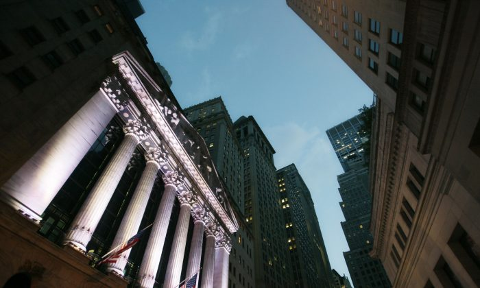 American flags fly in front of the New York Stock Exchange, in New York, on Oct. 8, 2014. U.S. stocks are opening sharply lower Tuesday, Dec. 9, 2014, following a slump in global markets. (AP Photo/Mark Lennihan)