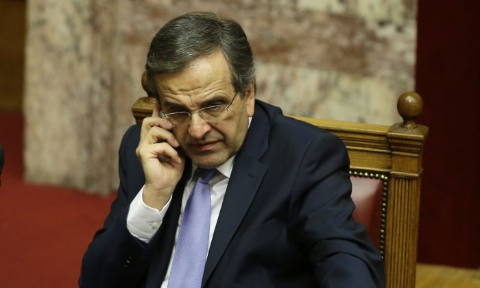 Greece's Prime Minister Antonis Samaras speaks on his cell phone after a parliament meeting for a vote on the country's 2015 budget in Athens on Dec. 8, 2014. In a televised address on Tuesday, Dec. 9, 2014, Samaras nominated Stavros Dimas, a senior figure in his conservative party and former EU commissioner for the environment, as the government's presidential candidate. Greek shares dived a day after the conservative-led government brought forward the date of a crucial presidential vote, raising a strong possibility of early general elections in the austerity-weary country. (AP Photo/Thanassis Stavrakis)
