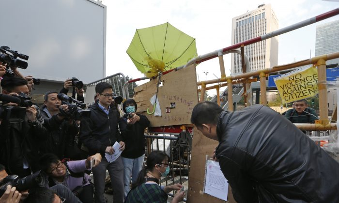 A bailiff member puts up an injunction document issued by a court, on a barricade set up by pro-democracy protesters at the occupied area outside government headquarters in Hong Kong Tuesday, Dec. 9, 2014. (AP Photo/Kin Cheung)