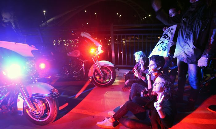 Protesters and police officers face off on a pedestrian bridge over Interstate 80 shortly after protesters shut down traffic in both directions in response to police killings in Missouri and New York in Berkeley, Calif., Monday, Dec. 8, 2014. (AP Photo/Noah Berger)