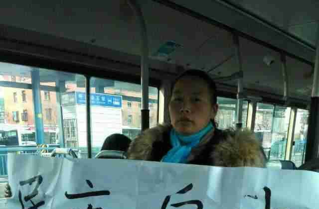 "Petitioner Wang Fang from Hubei Province holds a banner saying ""Democracy, freedom, human rights, constitution"" on a bus she was placed on by police in Beijing, on Dec. 4, 2014. It was China's newly established ""Constitution Day,"" but thousands of aggrieved petitioners found little to celebrate. (New Tang Dynasty Television)"
