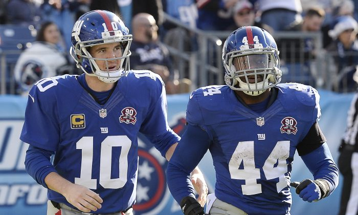 New York Giants quarterback Eli Manning (10) congratulates running back Andre Williams (44) after Williams scored a touchdown on a 50-yard run against the Tennessee Titans in the second half of an NFL football game Sunday, Dec. 7, 2014, in Nashville, Tenn. (AP Photo/Mark Zaleski)