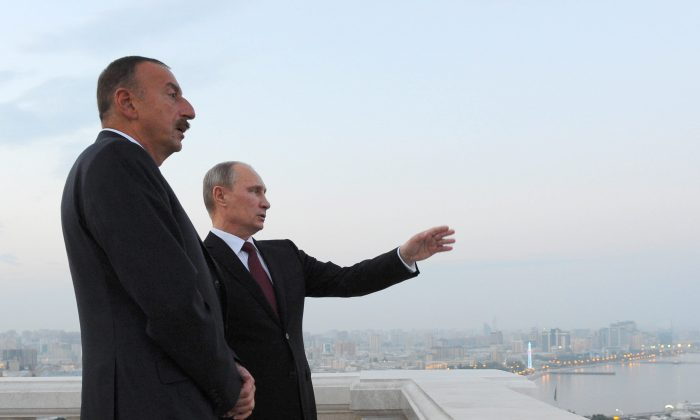 Russia's President Vladimir Putin (L) and his Azerbaijani counterpart Ilham Aliyev (R) speak as they walk in Baku, on Aug. 13, 2013. (Mikhail Klimentyev/AFP/Getty Images)