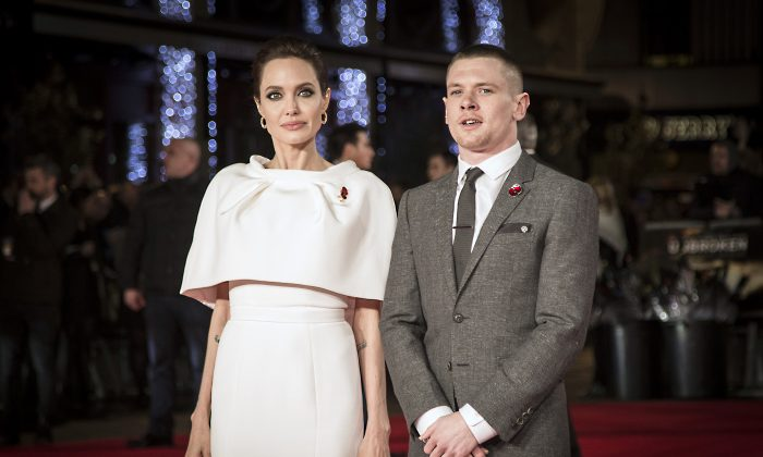 Actors Jack O'Connell, right, and Angelina Jolie pose for photographers upon arrival at the premiere of the film Unbroken in London, Tuesday, Nov. 25, 2014. (Photo by Vianney Le Caer/Invision/AP)
