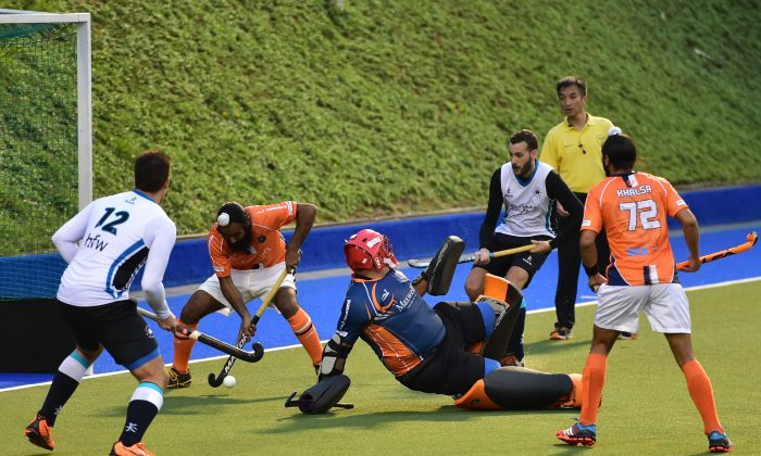An important stop by the Khalsa-A defence during their HKHA Premier Division match against HKFC-A at King's Park on Sunday Dec. 7, 2014. (Bill Cox/Epoch Times)